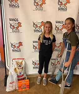 girls donate a dog and cat food at WAGS