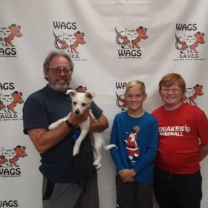 smiling kids and dad for new adopted white dog WAGS